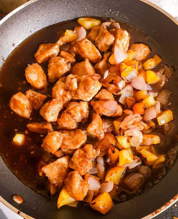 apple chicken stir fry with onions in a dark sauce on a frying pan