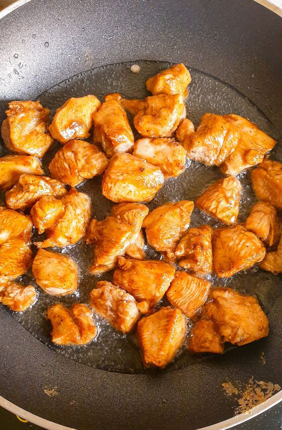 golden brown chicken cubes on a skillet being stir fried