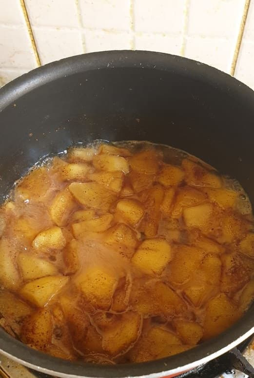 cooked apples with water in a sauce pan