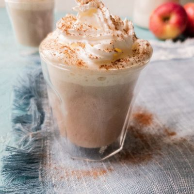 apple cinnamon latte in a glass topped with cream