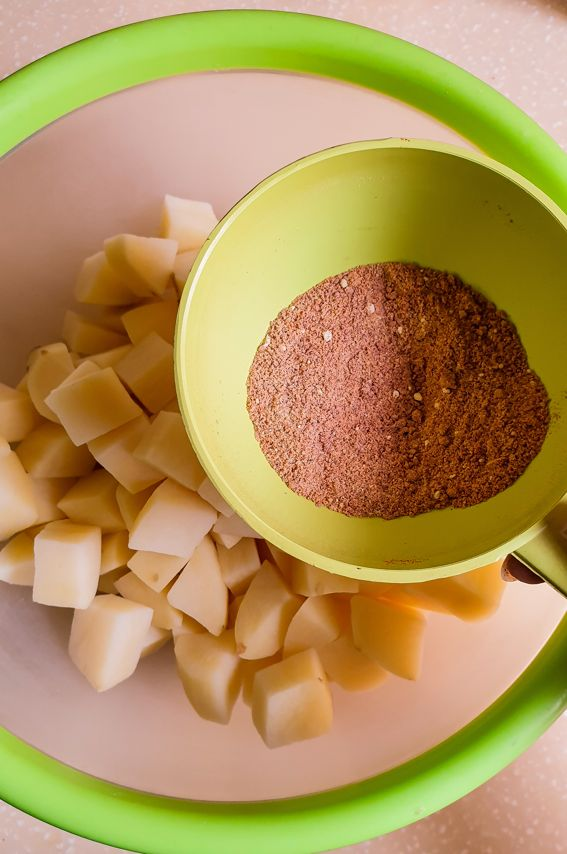 potato cubes in a bowl and a small bowl with a spice mix