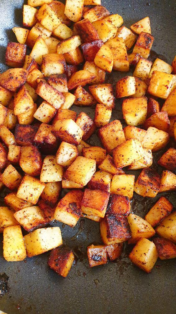 crispy golden brown batata harra on a fryin pan