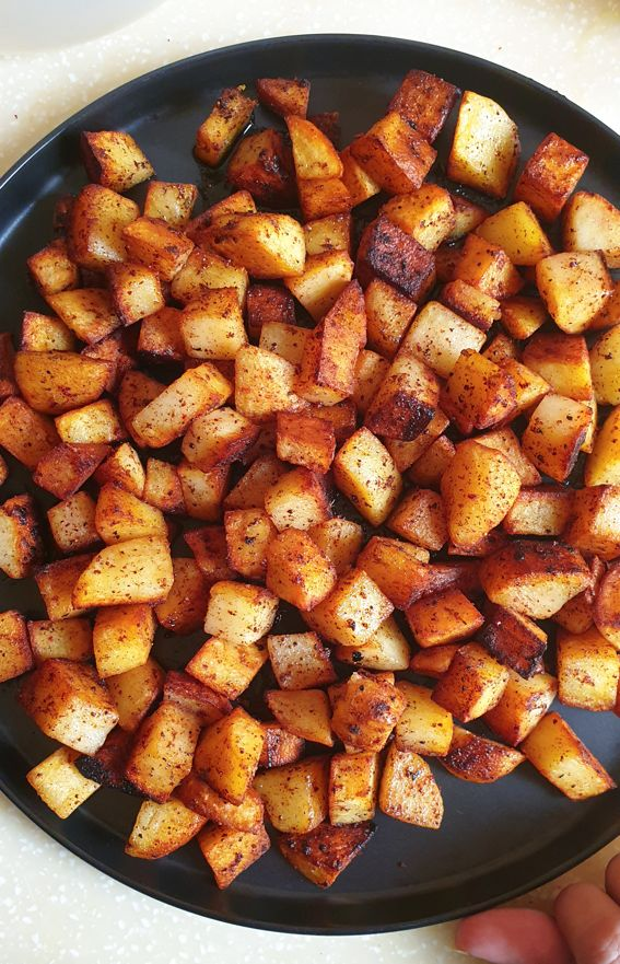 spicy pakistani style batata harra dished out on a black plate