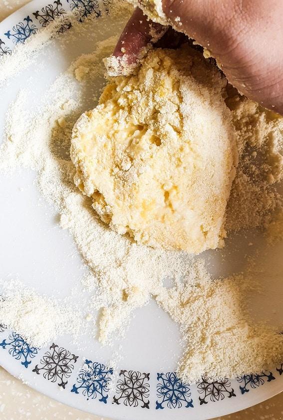Kneading milk balls for Rasmalai in a white dish