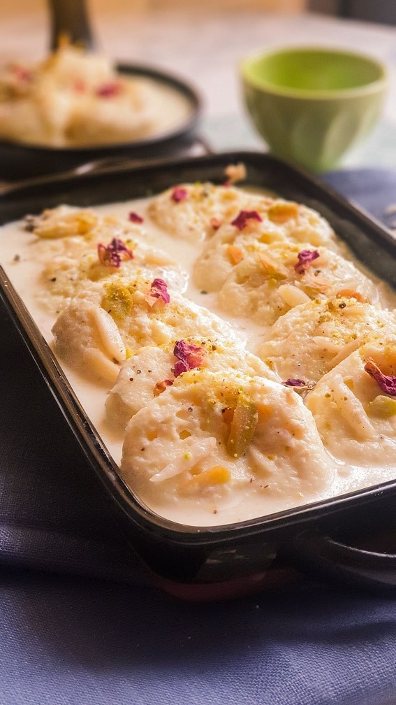Black Dish with rasmalai pieces in milk syrup, garnished with almonds and pistachios