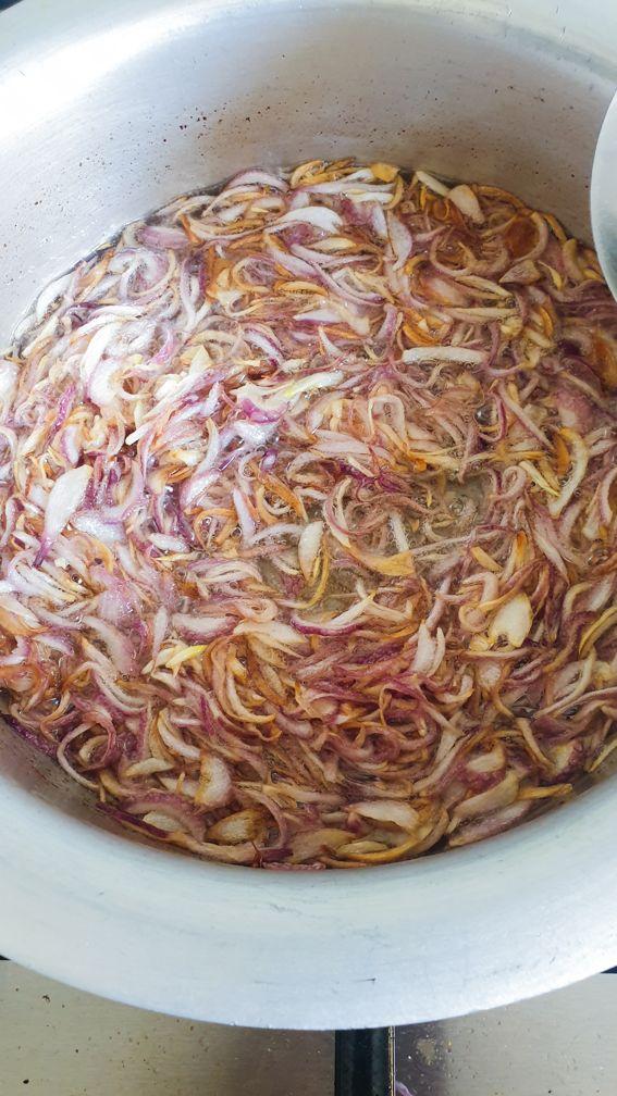 sliced onions in oil frying for making chicken ka salan