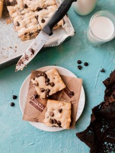 2 pieces of blonde chocolate chip brownie with a glass of milk on the side and a half showing tray of chocolate chip brownies with a few scattered chocolate chips all around a blue backdrop