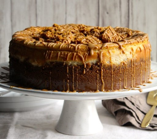A biscoff lotus cookie butter cheesecake on a white cake stand