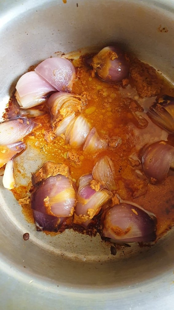 semi-cooked onions in oil in a steel cauldron