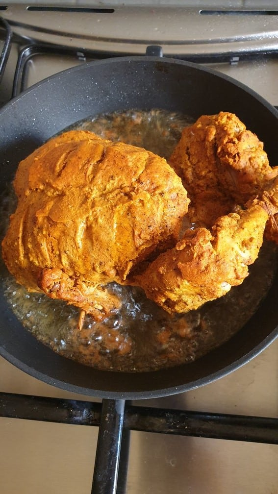 deep frying steamed chicken in a oil to make lahori chargha