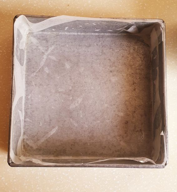 a square baking pan lined with a parchment paper (top view)