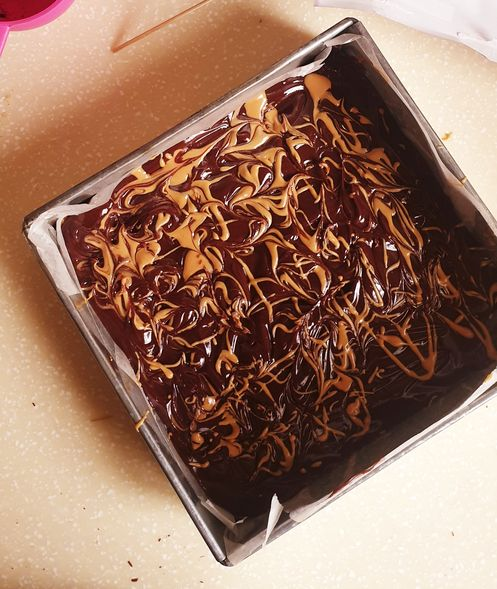 a top view of an un-set chocolate peanut butter bar dish in a square baking pan with peanut butter swirls on top.