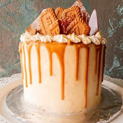 a front view of Lotus biscoff drip cake with caramel drip on a white iced cake, against a grey-blue backdrop