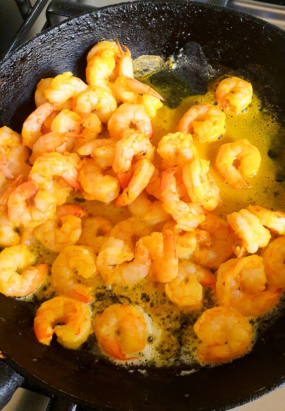 raw prawns in a black pan with butter for making prawn masala