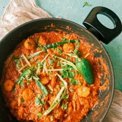a top view picture of prawn masala garnished with green chilies and ginger in a black wok, kept on top of a cream napkin against a light blue blackdrop
