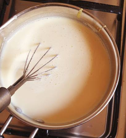 milk being boiled to make custard in steel pan with a whisk in it.