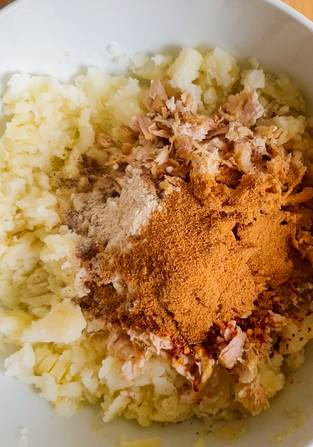 spices, shredded chicken and mashed potato in a white bowl