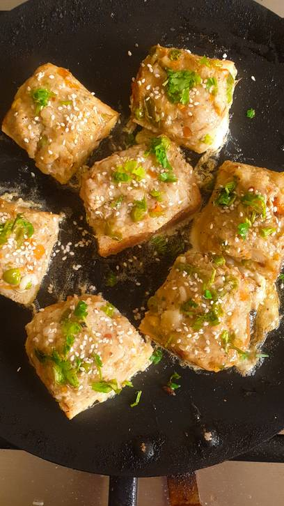 potato and bread snack squares, dipped in egg wash topped with coriander and sesame seeds in a frying pan with oil in it