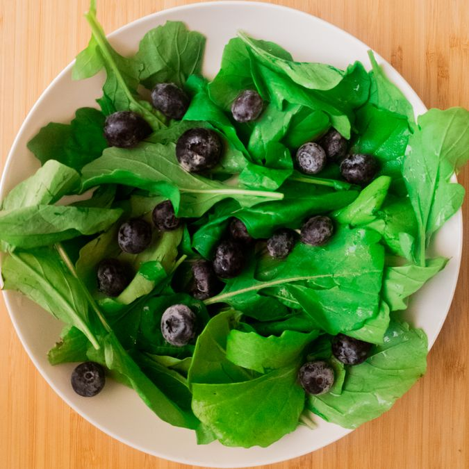 spinach and blueberry tossed in a bowl to make the spinach and berry salad