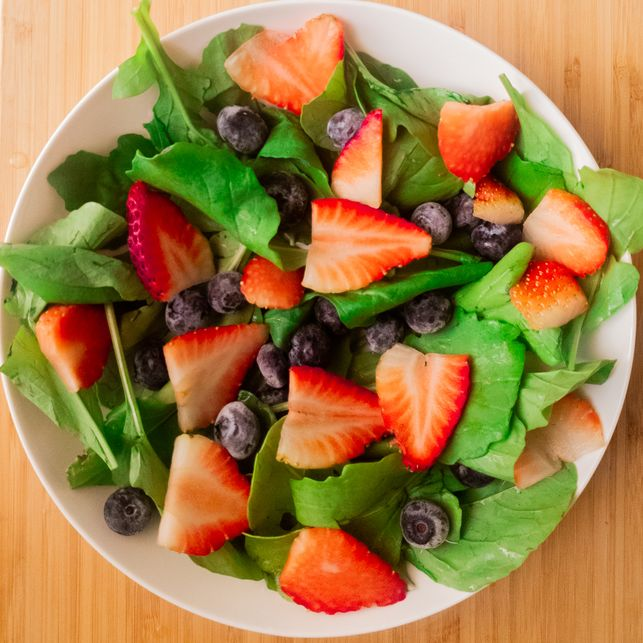 sliced strawberries, blueberries and spinach tossed in a white plate on a wooden board