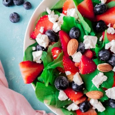 spinach and berry salad with feta cheese on a blue backdrop with a strawberry vinaigrette in a glass bowl on the upper left corner