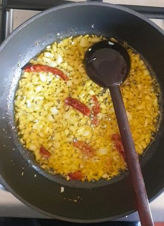 garlic, red chilies and shallots being fried in oil in a wok with a wooden spoon in it