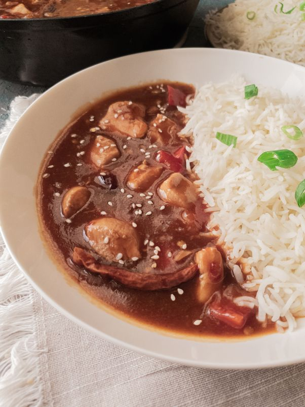 a side view of szechuan chicken gravy with white rice