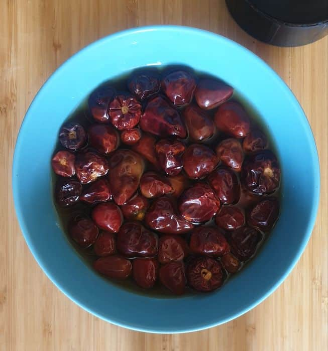 red chilies soaked in hot water in a blue bowl