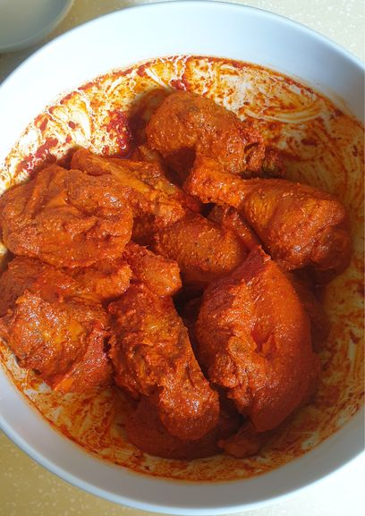 Chicken pieces marinated in tikka masala in a white bowl