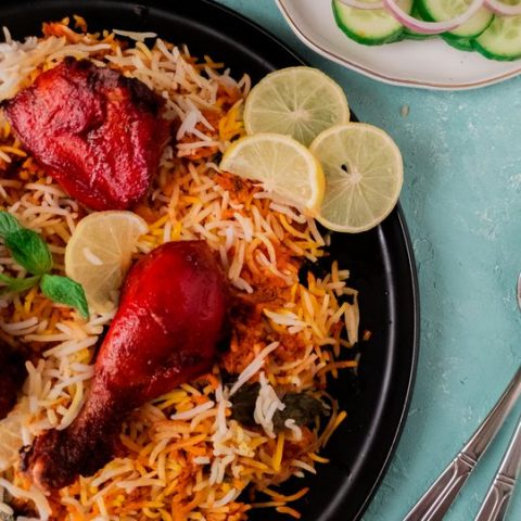 Close up of Pakistani Chicken Tikka biryani with lemons on the side