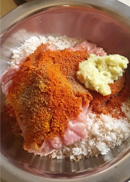 spices, garlic ginger paste covering raw chicken mince and bread crumbs in a steal bowl