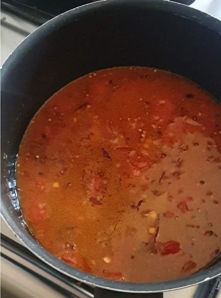 water and tomato gravy in a black pot