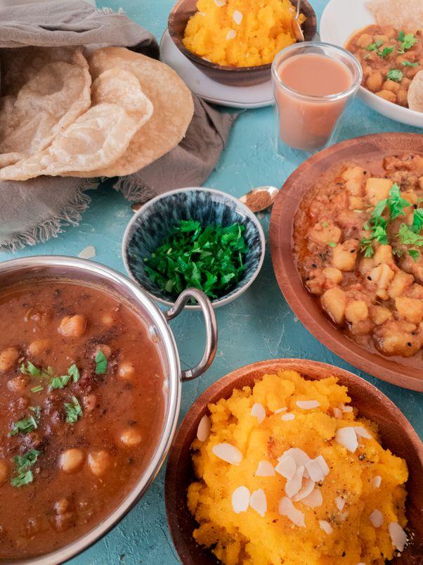an Indian / Pakistani breakfast buffet with aloo ki tarkari, cholay ka saaan, puri and sooji ka halwa