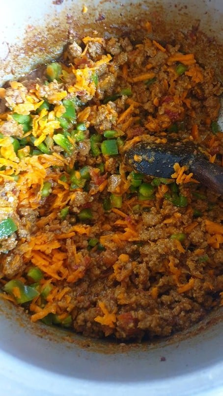 shredded carrot and chopped bell peppers strewn in a pot of minced beef