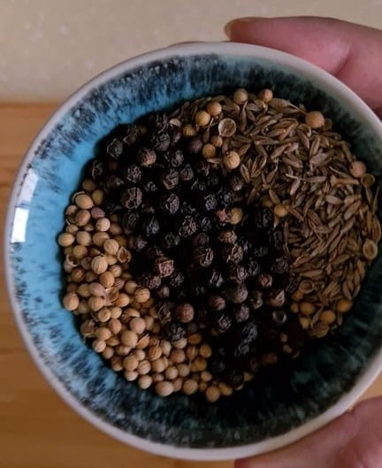 a blue bowl with coriander seeds, cumin seeds and black peppercorns