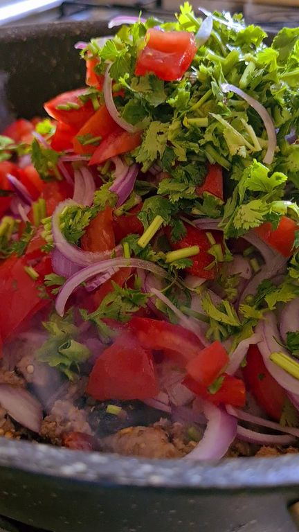 slices onions, chopped tomatoes and coriander tossed in ablack pan