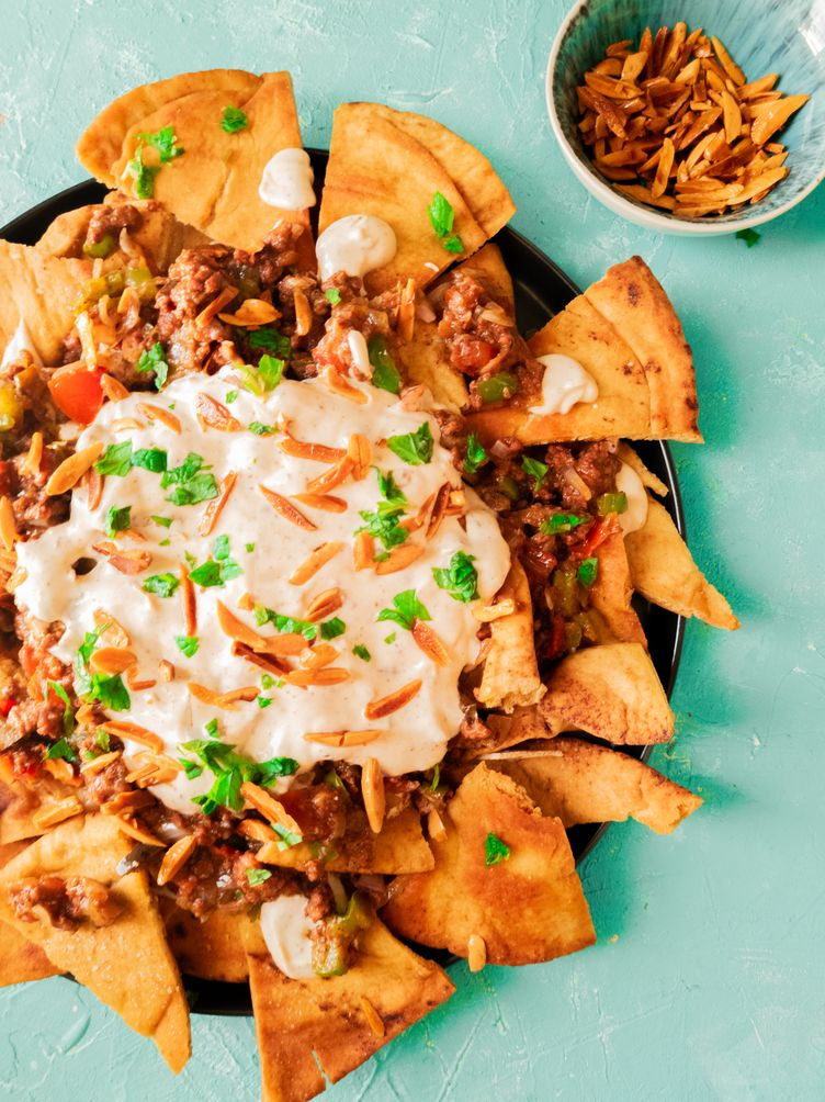 a plate of loaded nachos with white sauce and meat toppings on top of pita chips. Beef middle eastern nachos