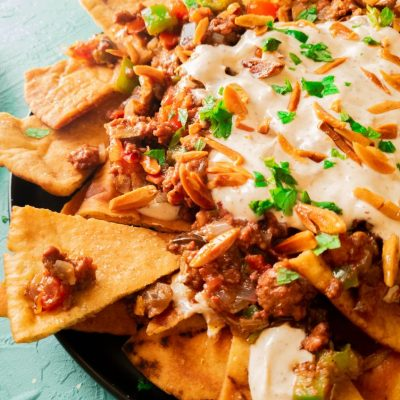 Triangle chips loaded with beef and veggies and white sauce along with garnish. Visible from a side