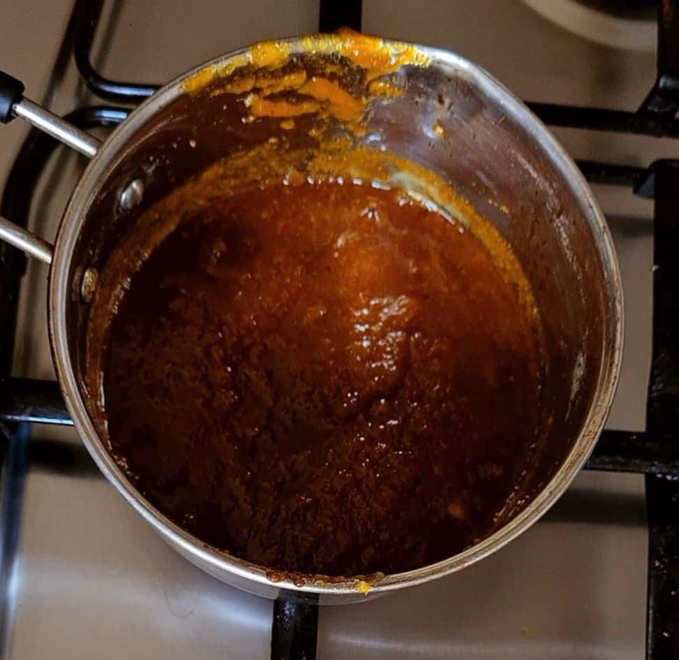 cooking pineapple sauce in a steel sauce pan