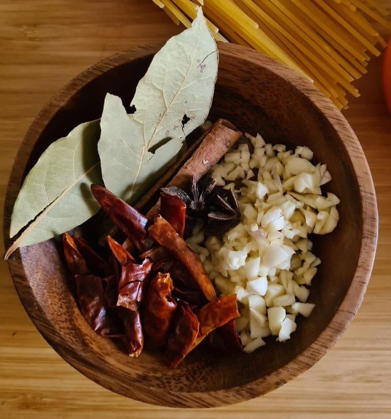 bay leaves, chopped garlic, red chilies and cinnamon stick
