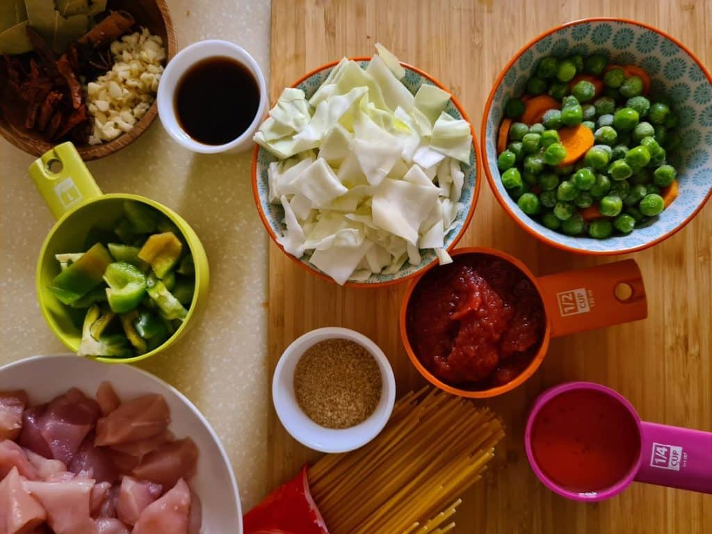 all the ingredients needs to make spicy chicken noodles laid out