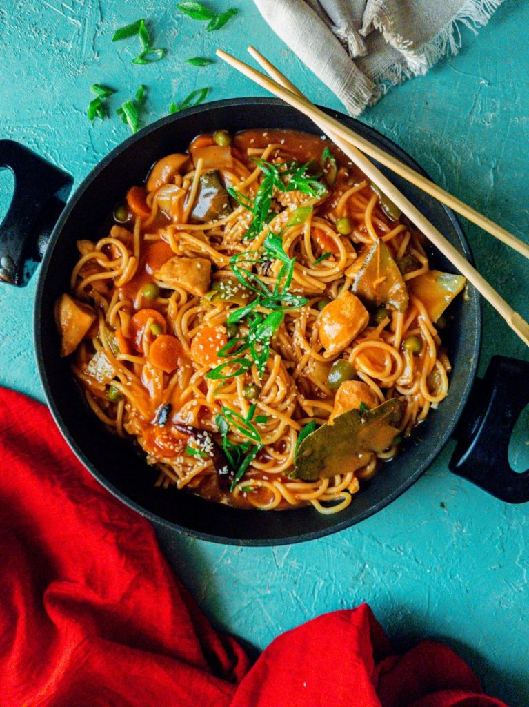 Spicy chicken and noodles in a pot with chopsticks on the side.