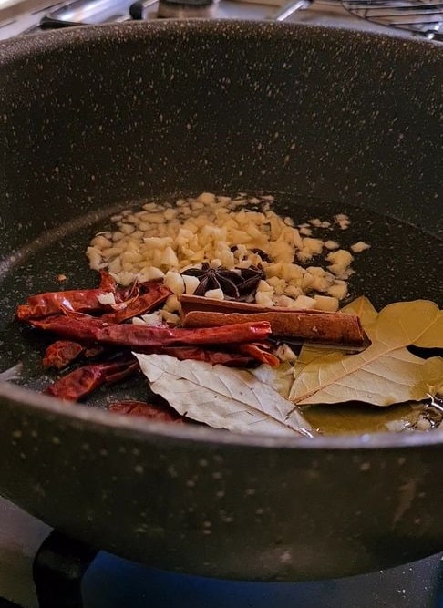 whole spices in the pot with oil