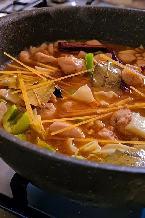 chicken, vegetables and raw noodles strewn around in a pot in a spicy broth.