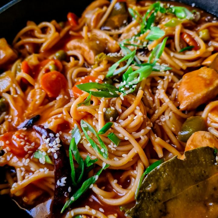 chicken vegetable and noodles in a black wok