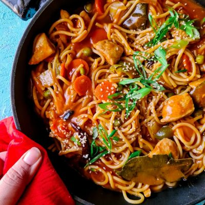 saucy noodles, chicken and vegetables in a black wok, topped with sesame seeds and green onions