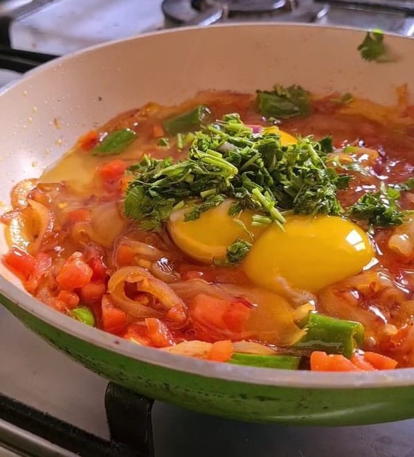3 raw eggs and chopped cilantro sitting on a bed of spiced onions and tomatoes
