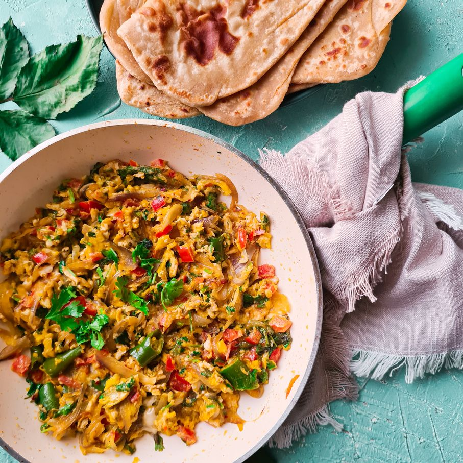 khageena in a pan with some parathas on the side