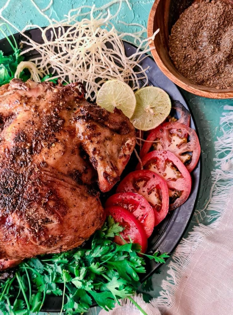Balochi Chicken sajji in a black plate with tomatoes and coriander