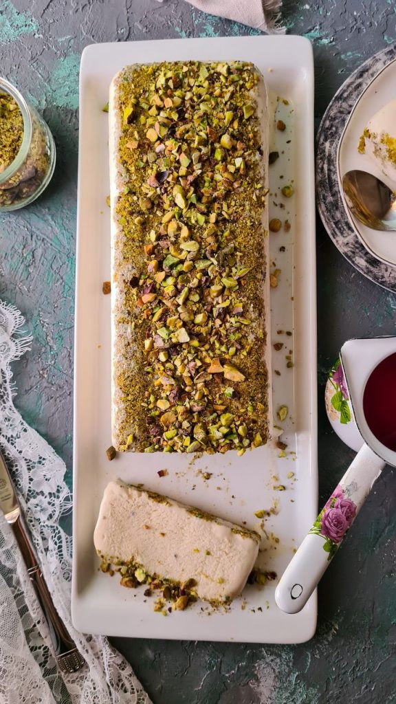 top view of a malai kulfi terrine with a slice cut up on the side. the terrine is covered with pistachios